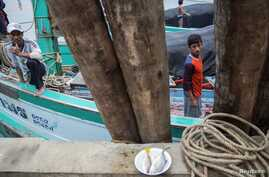 FILE - Migrant fishermen from Myanmar work on a boat after returning from the ocean to Ban Nam Khem, Thailand, Dec. 14, 2014.