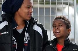 FILE - Tenjin, right, an 11-year-old Eritrean boy who arrived on a boat from Tripoli without his parents, waits with another young migrant at the port of Lampedusa to board a ferry bound for Porto Empedocle in Sicily, February 20, 2015.