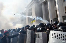 FILE - A demonstrator holds a police officer's shield in front of the parliament building in Kyiv as smoke rises from the building during clashes with police officers on August 31, 2015.