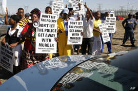 A group of protestors holds placards as a large crowd follows retired judge Ian Farlam and his team as they inspect the area where the bodies of mine workers were found after the shootings at Lonmin's platinum mine in Marikana near Rustenburg, South