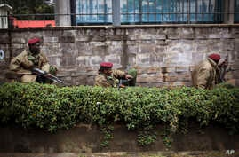 Kenya security forces are seen behind a wall outside the Westgate Mall in Nairobi, Sept. 23, 2013.