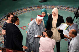 Abdelfattah Mouro, center, deputy president of the Tunisian Assembly, speaks with deputies during debate on anti-terror legislation at the assembly in Tunis, July 24, 2015.