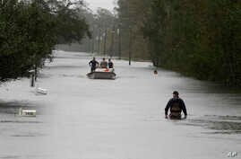 A member of the U.S. Coast Guard walks down Mill Creek Road checking houses after Tropical Storm Florence hit Newport, N.C., Sept. 15, 2018.