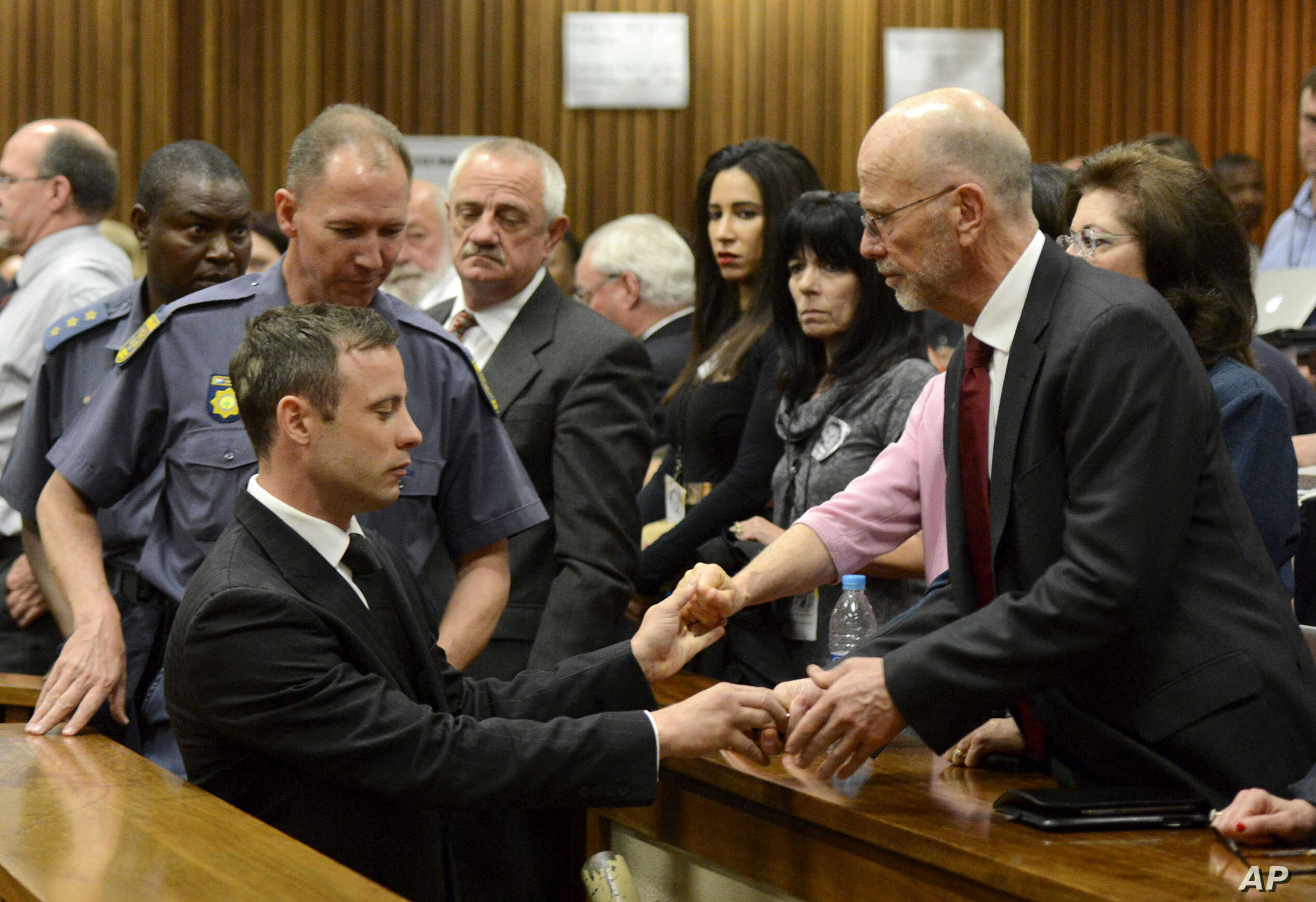 Oscar Pistorius, left front, greets his uncle Arnold Pistorius, right, and other family members as he is led out of court in Pretoria, South Africa, Oct. 21, 2014. Pistorius received a five-year prison sentence for culpable homicide by Judge Thokozil