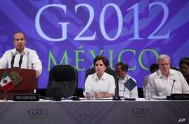 Mexico's President Felipe Calderon, left, delivers a speech during the G20 foreign ministers summit in Los Cabos, Mexico, Feb. 20, 2012