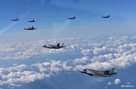 U.S. Marine Corps F-35B fighter jets (front) and South Korean air Force's F-15K fly over South Korea during a joint military drill, South Korea, Aug. 31, 2017.
