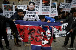 FILE - Protesters tear a defaced North Korean flag during an anti-North Korean rally in central Seoul, South Korea, Nov. 23, 2015. In the wake a group defection by 13 North Koreans, South Korea has warned its citizens of a hightned threat of abductio