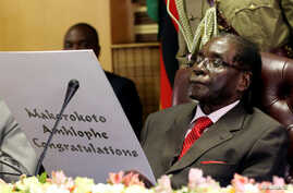 Zimbabwe's President Robert Mugabe reads a card during his 93rd birthday celebrations in Harare, Zimbabwe, Feb. 21, 2017.