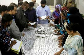 Pakistani election staff count the votes after polls closed at a polling station for the parliamentary elections in Karachi, Pakistan, July 25, 2018.