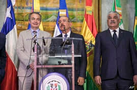 Dominican Republic President Danilo Medina, center, addresses the press alongside Jose Luis Rodriguez Zapatero, former prime minister of Spain, left, and Miguel Vargas, Dominican Republic foreign minister, after a long day of negotiations aimed at re