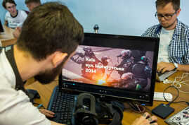 Staff members of New Cave Media test a virtual reality simulator in their office in Kyiv, Ukraine, Sept. 11, 2018. The simulator provides a VR reconstruction of the 2013-14 demonstration in Ukraine, when dozens of protesters were killed in the final