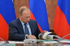 FILE - Russian President Vladimir Putin looks through a book during meeting with senior government officials in Magas, regional Ingushetian capital, Russia, Sept. 13, 2015.