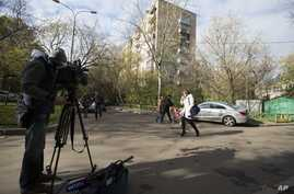 A cameraman films a view of the building where homemade explosives were found in an apartment, in Moscow, Russia, Oct. 12, 2015.