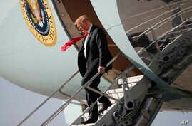 President Donald Trump walks down the stairs of Air Force One during his arrival at Palm Beach International Airport, in West Palm Beach, Florida, March 29, 2018. Trump is spending the weekend at his his Mar-a-Lago estate.
