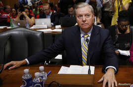 Senator Lindsey Graham waits at the witness table as chanting disabled protesters are removed by Capitol Hill police before a Senate Finance Committee hearing on the Graham Cassidy bill to repeal and replace the Affordable Care Act on Capitol Hill in