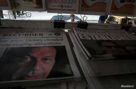 FILE -A man looks at newspapers at a stall a day after general election in Islamabad, Pakistan, July 26, 2018.