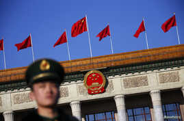 FILE - A paramilitary policeman stands outside the Great Hall of the People in Beijing.