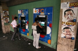 FILE - People withdraw money from cash machines where election propaganda supporting Venezuela's President Hugo Chavez cover the nearby walls in Caracas, Venezuela, Feb. 8, 2013.