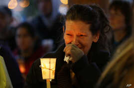Teresa Welter cries as she holds a candle at a vigil for mudslide victims in Arlington, Washington, March 25, 2014.