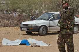 A member of the Kenyan security forces speaks on a telephone next to the body of one of those killed, outside the African Inland Church in Garissa, Kenya, July 1, 2012.