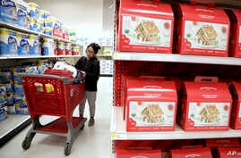 FILE - A shopper looks at an item before placing it in her cart during a trip to a Target store in Edison, N.J., Nov. 16, 2018. Slower consumer spending is seen as the biggest factor in the fourth-quarter economic slowdown.