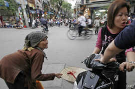 FILE - An older Vietnamese woman begs for money on a busy Hanoi street.