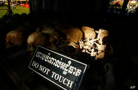 """In this photo taken, May 20, 2013, hundreds of former Khmer Rouge victims' bone and skulls are displayed in a memorial at Choeung Ek """"Killing Field"""" in Phnom Penh, Cambodia."""