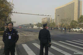 Police stand guard in front of the Shanxi Provincial Communist Party office building after explosions in Taiyuan, Shanxi Province, Nov. 6, 2013.