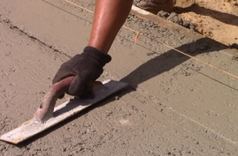 A worker smooths the concrete foundation of a new house.