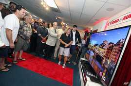 Jay Vandenbree, head of LG Electronics' U.S. consumer electronics business, fourth from right, gives consumers a look at the first Ultra-High-Definition TV to hit the U.S. market, an 84-inch LG model sold at Video & Audio Center in Lawndale, Californ