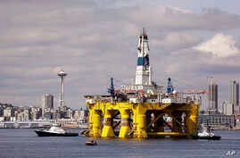 FILE - The Royal Dutch Shell oil drilling rig Polar Pioneer is towed toward a dock in Elliott Bay in Seattle. Royal Dutch Shell reported a third quarter loss of $7.4 billion, Oct, 29, 2015, as it re-organized and canceled projects, including drilling