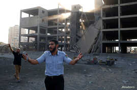 A Palestinian policeman loyal to Hamas reacts in front of a building that was hit in an Israeli airstrike in Gaza City, July 14, 2018.