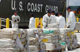 FILE - In this Aug. 2, 2011 photo, U.S. Coast Guard crew members unload roughly 7.5 tons of cocaine, in Miami Beach, Fla., which was seized from a submarine-like craft off the Caribbean Coast of Honduras.