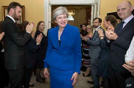 Britain's Prime Minister Theresa May is applauded by staff as she returns to 10 Downing Street, after seeking permission from Queen Elizabeth to form a new government, in London, June 9, 2017.