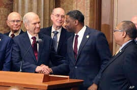 Mormon church President Russell M. Nelson shakes hands with Derrick Johnson, president of the NAACP during a news conference, May 17, 2018, in Salt Lake City.