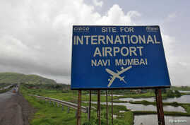 A signboard is pictured at the proposed site of Navi Mumbai airport, about 45 km (27 miles) east of Mumbai, August 8, 2012.
