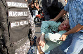 Teodoro Campos, opposition lawmaker and security chief of Venezuelan presidential candidate Henri Falcon, receives help after sustaining an injury during a rally with Falcon, in Caracas, Venezuela,April 2, 2018.