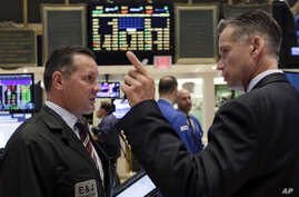 Traders on the floor of the New York Stock Exchange react to market changes, Aug. 25, 2015.