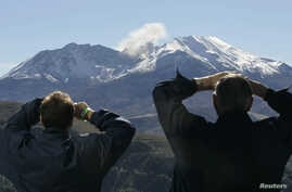 FILE - Visitors to the Coldwater Ridge Center look up at Mount St. Helens venting steam, Oct. 11, 2004.