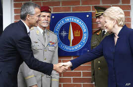 NATO Secretary General Jens Stoltenberg (L) shakes hands with Lithuania's President Dalia Grybauskaite, after unveiling the NATO Force Integration Unit plaque on its headquarters building in Vilnius, Lithuania, Sept. 3, 2015.