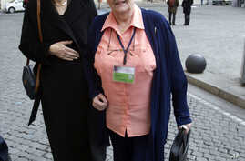 FILE - Marie Collins, right, who was assaulted as a 13-year-old by a hospital chaplain in her native Ireland, is flanked by British psychiatry professor Sheila Hollins, as they arrive at a Vatican-backed symposium on clerical sex abuse, in Rome, Feb.