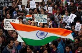Indian students wave an Indian flag and shout slogans during a protest at the Jawaharlal Nehru University against the arrest of a student union leader in New Delhi, India, Thursday, Feb. 18, 2016.