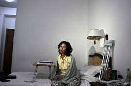 FILE - Ni Yulan sits on the bed in a hotel in Beijing.