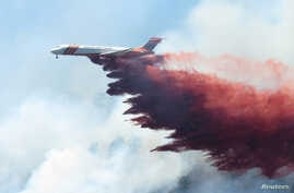 A plane drops fire-retardant chemicals on the 416 Fire near Durango, California, in this June 9, 2018, handout photo.
