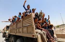 Volunteers, who have joined the Iraqi Army to fight against the predominantly Sunni ISIL militants, travel in army trucks in Baghdad June 14, 2014.