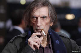 "FILE - Actor Harry Dean Stanton smokes a cigarette as he poses at the world premiere of the film ""Marvel's The Avengers"" in Hollywood, California, April 11, 2012."