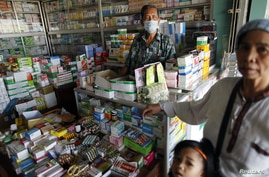 A man wears a mask as he waits for customers at his drugstore in Pailin in western Cambodia, January 2010. (file photo)