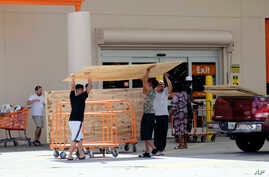 Customers buy plywood sheets to protect their homes at a Home Depot in Florida City, Fla., Sept. 8, 2017. Hurricane Irma weakened slightly Friday but remained a dangerous and deadly hurricane taking direct aim at Florida.