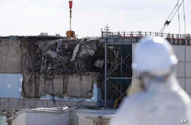 A member of the media tour group wearing a protective suit and a mask looks at the No. 3 reactor building at Tokyo Electric Power Co's (TEPCO) tsunami-crippled Fukushima Dai-ichi nuclear power plant in Okuma, Fukushima Prefecture, Japan, Feb. 10, 201...