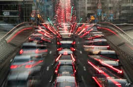 FILE - In this slow-shutter zoom effect photo taken Dec. 12, 2018, commuters backed up in traffic during the morning rush hour, in Brussels, a city that regularly experiences pollution alert warnings.